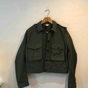 Mossgrön militärjacka i tunt material. Snygg passform. Resår i bak. Använd ett fåtal gånger.