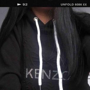 """Kenzo hoodie köpt utomlands för ett högre pris. Tjockt material och skönt foder inuti så passar fint till sommarens kvällar. Fattas en svarowski i """"O"""" men kan enkelt ersättas med nageltillbehör osv! Använd en enstaka gång. INTE ÄKTA"""