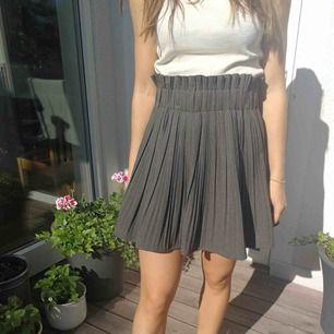 Veckad kjol med stretch i midjan, aldrig använd.