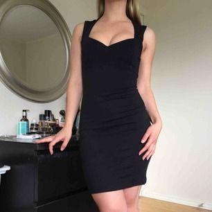 Stretchig, svart fodralklänning med fin skärning i halsen. Använd en gång.