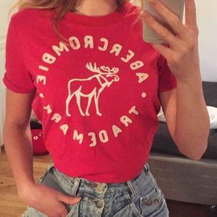 T-shirt från abercrombie & fitch i storlek S. Fin röd färg med vit text och en älg. Riktigt bra kvalitet och bra material. Nypris 250kr men säljer den för 110kr och köparen står för frakten.