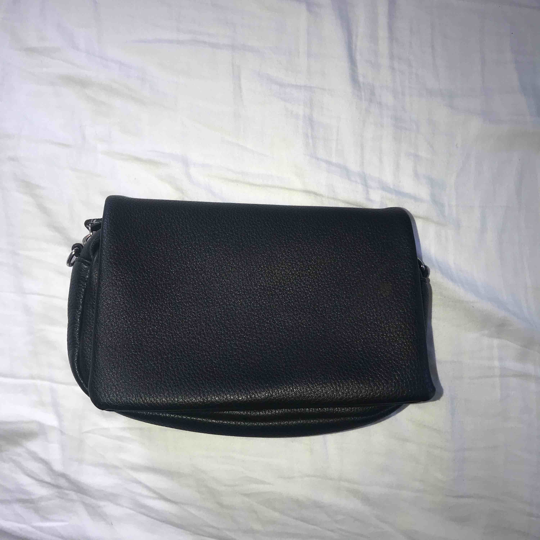 Superfin svart läder väska. Silver detaljer och krokar att hänga på nytt axelband i.  Köptesför 130kr säljer för 70kr inkl frakt. Bild 1 framsida Bild 2 insida Bild 3 baksida. Väskor.