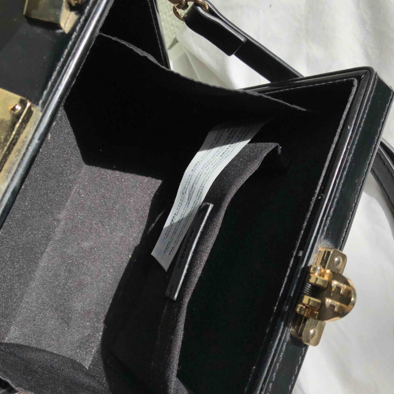 Svart väska i portföljdesign. Väldigt sparsamt använd. Se bilder för insida, storlek och remlängden på väskan. Vid flera köpare så går köpet till högst bud. Möter gärna upp i Stockholm, annars står köparen för tillkommande frakt, 72kr:). Väskor.