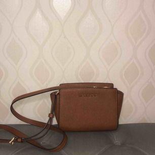 En liten brun väska med axelband. Nypris 2000kr säljs 850kr nyskick! (ÄKTA) köpt i original butik!   Vid intresse fler bilder finns!   Köparen står för frakt!