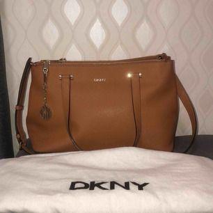 Brun DKNY Väska. Nypris 3000kr säljs 1250kr. Väskan är i nyskick (ÄKTA).  Vid intresse fler bilder finns! Köparen står för frakt!