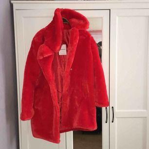 Röd oversized päls kappa från Nelly. Oanvänd.
