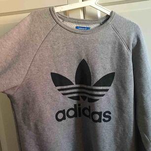 Grå Adidas sweatshirt storlek M (Male size) Säljs pga sällan användning då den är för stor. Små fläckar (se bild 3) Skriv DM för info om betalning osv.