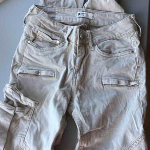 Ett par lågmidjade beigha  jeans med ficka på ena låret. ifrån Gina tricot. Oanvända. Köpta för 499kr med säljer för 120kr. Pris kan diskuteras!