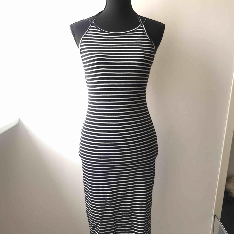 Randig klänning med öppen rygg. Halterneck men knytning i bak och reglerbara axelband. Klänningen går över knäna. I mycket fint skick! Köparen står för frakten 🦋. Klänningar.