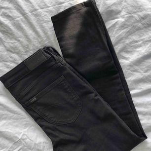 Svarta Lee-jeans i modellen Scarlett Cropped. Köpta för 700 kr på MQ för 2 år sen. Aldrig använda så i nyskick. Tight passform + normalhöga i midjan. Slutar en bit över fotknölen på mig (168cm). Jag har 27-28 i jeans o dessa passar bra.   Pris inkl. frakt