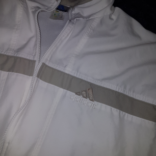 Vit och grå Adidasjacka. Adidasmärket finns både på framsidan och på ryggen. Har en liten fläck på ena ärmen. 300 kr, kan mötas upp i sthlm eller skickas (köparen betalar portot) 🌟