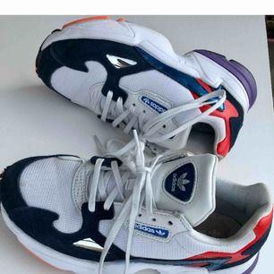 Vita Adidas Falcon i gott skick (använda 3-4 gånger). Skorna är ljusare irl än på bilderna. Storlek 38 2/3.  Lila, röda, blå och oranga detaljer. Finns i Hägersten, köparen betalar ev frakt. Betalning via swish eller kontant.  Ord pris 1 000 kr.