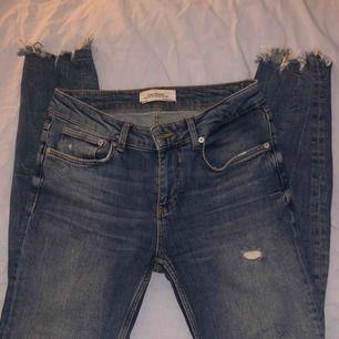 Jeans från Zara i strl 36. Hål vid höger knä och slitningar nedtill. Når till fotknölen på mig som är 168. Sparsamt använda så i fint skick! 200 kr inkl. frakt.