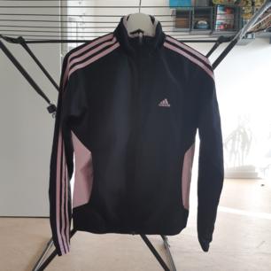 Adidaströja/jacka i svart och ljusrosa, i gott secondhandskick förutom lite slitage på kragen!