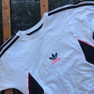 Adidastshirt med starka rosa detaljer köpt på Footlocker. Använt några gånger men det syns inte alls, den är som ny.