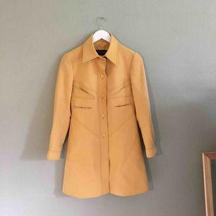 Gul mycket stilig kappa i 50-tals stil . Figursydd och lätt utställd nertill. Köpt i en vintageaffär för 600 kr men aldrig använts. Utmärkt skick