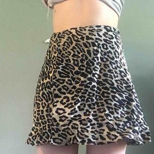 Kort kjol med leopardmönster  i glansigt material. Nuvarande bud 90 kr