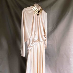 SATIN SET Persiko/puderrosa kjol och blus i gott skick. Perfekt till finare tillställningar. Midja kjol: 33 cm. Resår i midjan på blus, kan enkelt tas bort om du vill det. Knappar i halsen. Vid fler intressenter går köpet till den som läger högst bud.