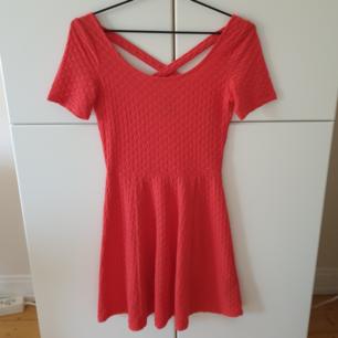 Söt och somrig klänning från H&M's Divided i koralfärg. Tyget har ett slags mönster (se bilder) och i ryggen är det ett kors. Använd ytterst fåtal gånger, ser oanvänd ut. Storlek 34 (XS). 50 kr + frakten <3