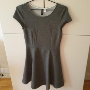 Grå klänning från H&M's Divided. Tyget har ett slags mönster (se bilder) och är åt ett tjockare håll men funkar ändå under sommaren! Använd max 2 gånger, alltså i nyskick! Storlek 34 (XS). 50 kr + frakten <3