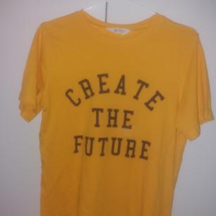 En jätte fin gul t-shirt med trycket create the future