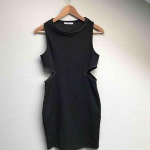 Svart klänning med öppning i midjan. Liten i storleken.
