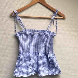 Blå/vitrutigt linne med knytband. Knappt använd. Resor/stretch över bröstpartiet.