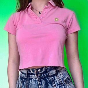 En croppad rosa piké med en grön broderad blomma🍀 Märkt som en M men passar bäst XS/S. Fri frakt!