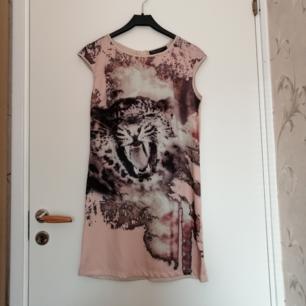 Beige tigermönstrad klänning, aldrig använd. Passar M bättre än S. Har en liten reva vid halslinningen bak på höger sida
