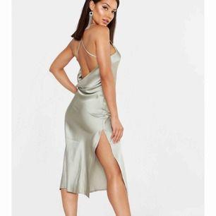 Aldrig använd superfin satin klänning i färgen dusty green. Den har en slits vid ena benet och en öppen rygg. Säljs då jag beställde den i fel strl  Köparen står för frakt :)