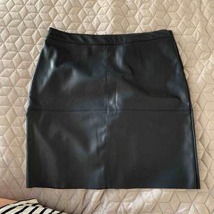 Mörkblå kjol i läderimitation från Carin Wester. Fint skick  Köparen står för frakt.