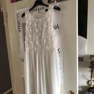 En jättefin vit klänning som har blommor på överdelen och är öppen i ryggen!