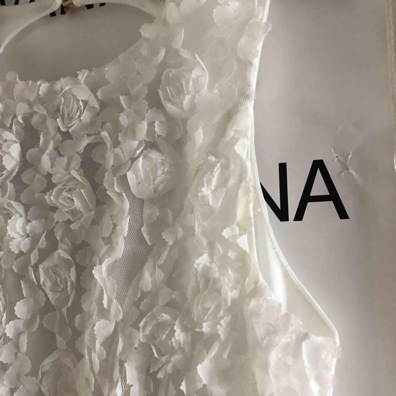 En jättefin vit klänning som har blommor på överdelen och är öppen i ryggen! . Klänningar.
