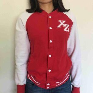 En rödvit collegetröja från H&M med trycket XZ, den har även knappar av metall fram på tröjan. Kostar 149kr inklusive frakt.