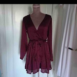 Jättefin och somrig vinröd omlott satin klänning från Nelly. Kan mötas upp annars står köparen för frakten❣️