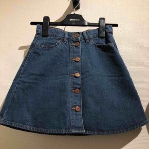 A-linje skuren jeanskjol med knappar från Monki! I jättefint skick. Riktiga fickor fram och bak