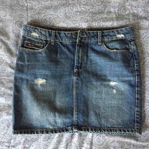 Fin jeanskjol med slitna detaljer. Nyskick. Storlek 38 men passar både 36-38. Djupa framfickor. Frakt ingår.