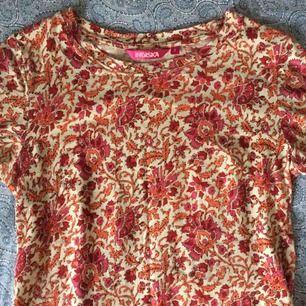 Mönstrad t-shirt från Indiska. Färgerna går i rött, orangeröd rosa på en beige bakgrund. Frakt ingår.