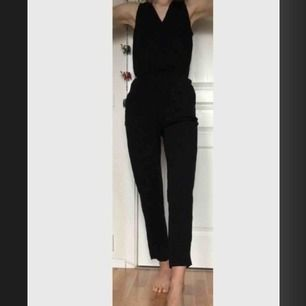 Jättefin svart jumpsuit med spetsdetaljer axlar/rygg. Fickor fram. Liten tryckknapp som inte syns i v-ringningen. Bara axlar och långa ben. Jag är 179 lång. Frakt ingår.