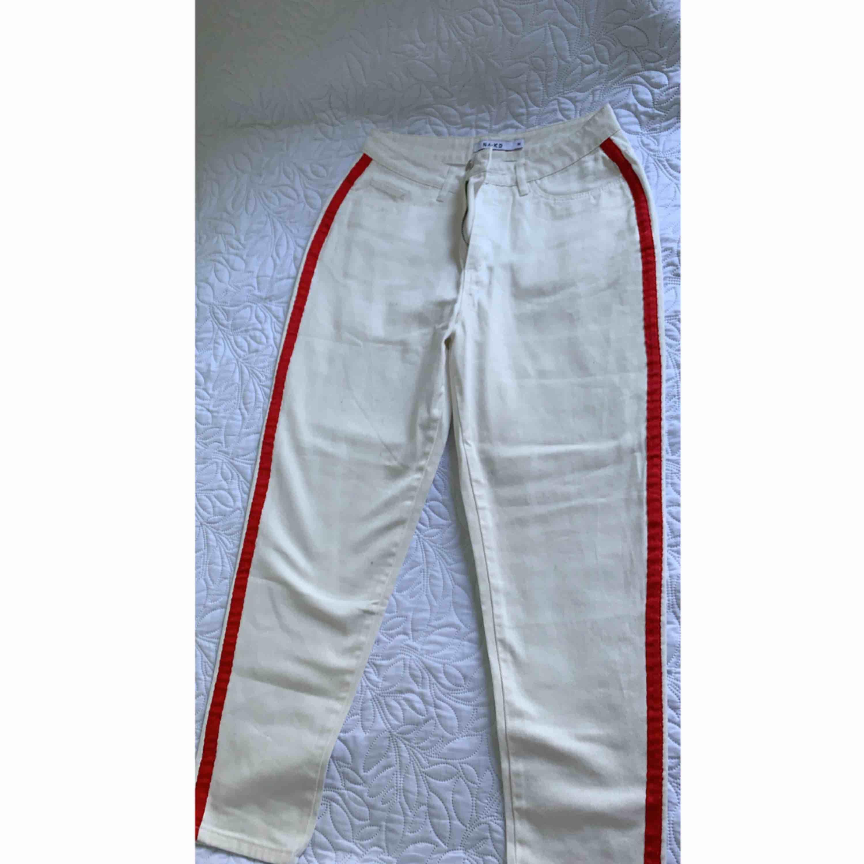 Säker vit byxa med röda band på sidan. Byxan är aldrig använd och är i bra skick. Köparen står för frakten . Jeans & Byxor.