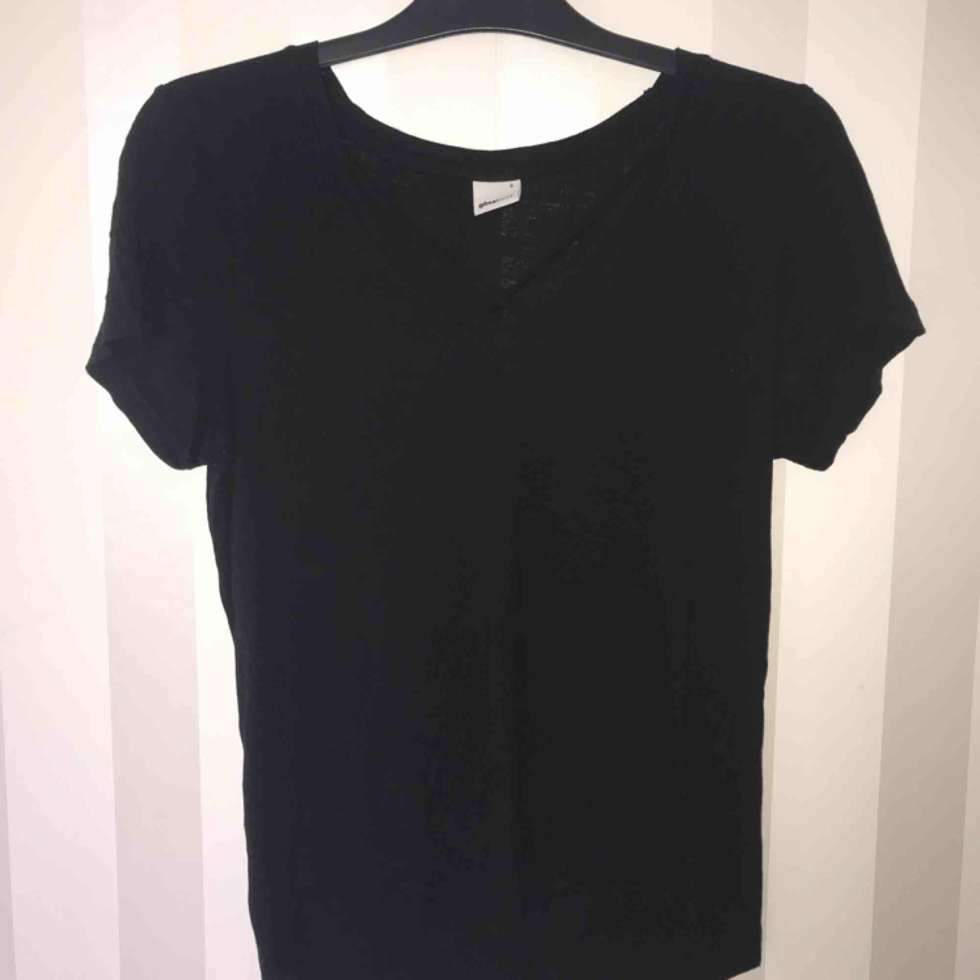 Vanlig svart tisha med korsning i halsringningen.. T-shirts.