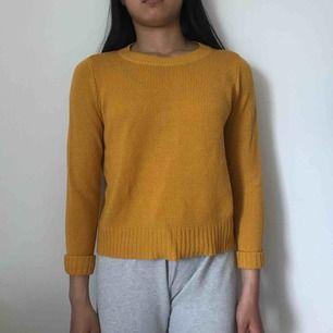 En stickad senapsgul tröja som kostar 100kr inklusive frakt.