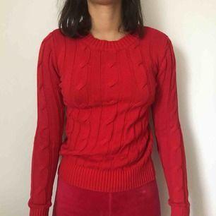 En röd stickad tröja från Gina Tricot. Kostar 100kr inklusive frakt.