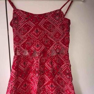Röd klänning med svarta mönster, trianglar som hål vid magen/under brösten. Har en likadan i svart. Fler bilder vid intresse, köparen står för frakten.