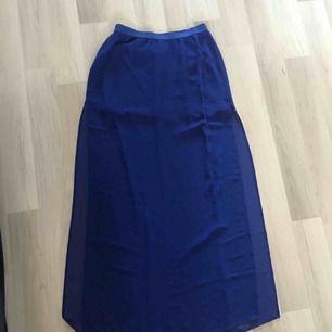 En supercool blå kjol med en kortare innerkjol och genomskinlig överkjol. Det är två slitsar på sidorna. Frakt tillkommer
