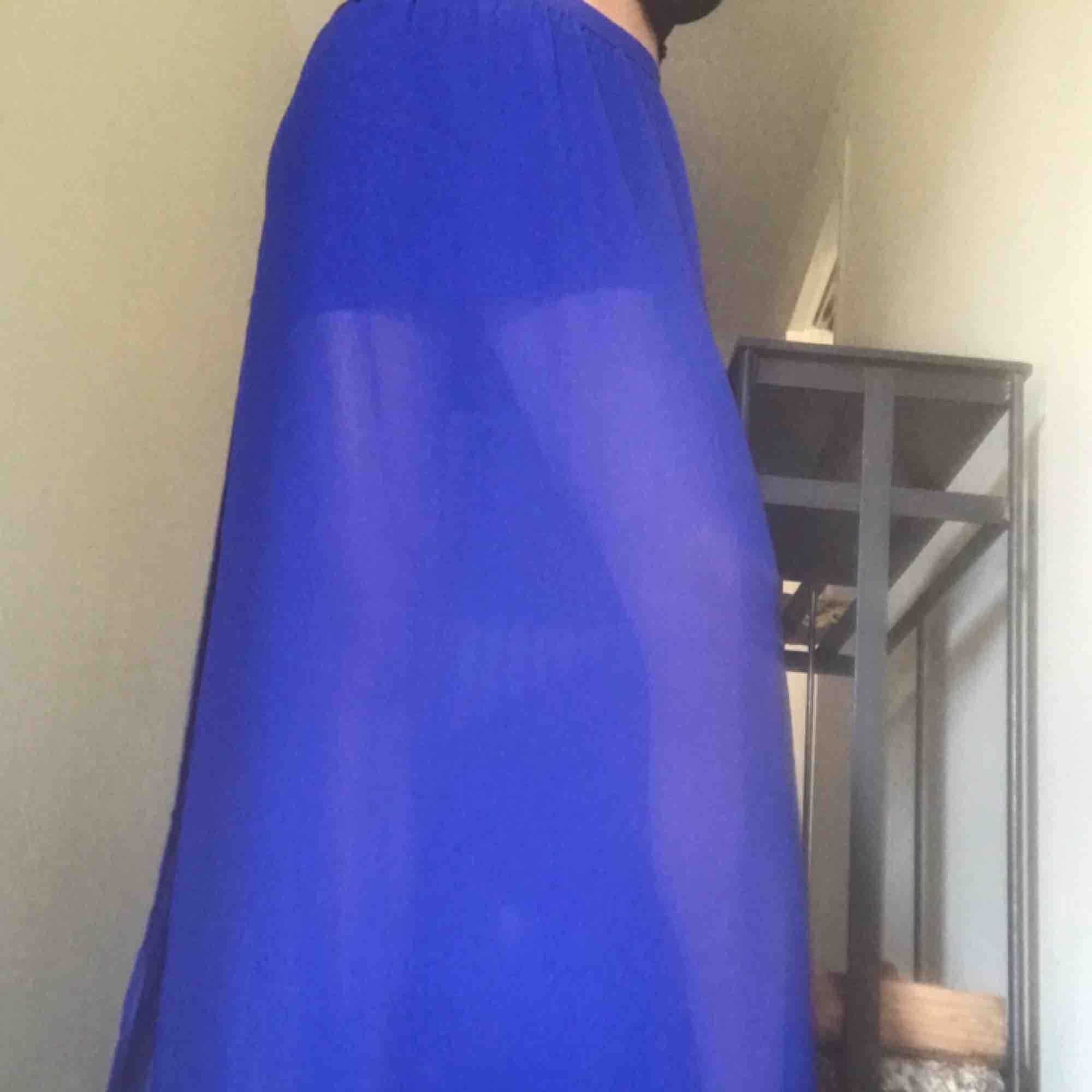En supercool blå kjol med en kortare innerkjol och genomskinlig överkjol. Det är två slitsar på sidorna. Frakt tillkommer. Kjolar.