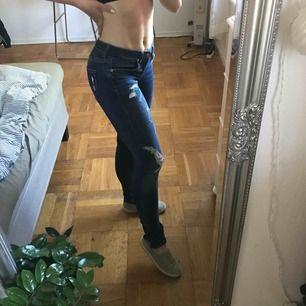Slitna mörka jeans från GinaTricot. Använda ett fåtal gånger och är i bra sick. Dragkedja längs med vristen. Riktiga fickor både bak och fram. Vid köp tillkommer fraktkostnad.