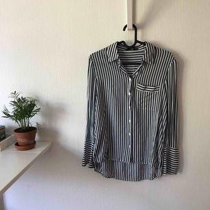 Randig skjorta från Mango med bröstficka (från bildens håll) höger sida. Annorlunda men snygg avslutning på skjortans armar. Använd en gång och är i mycket bra skick. Vid köp tillkommer fraktkostnad.