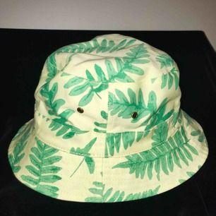 Bucket-hat som kan vändas ut och in för olika mönster. Aldrig använd.