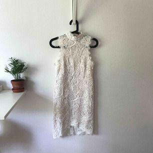 Vit spetsklänning från Chiquelle med mönster på. Hög i halsen med dragkedja fram. Längre bak än fram. Hudfärgat tyg inuti och är därför inte genomskinlig. Nypris: 599kr  Vid köp tillkommer fraktkostnad.